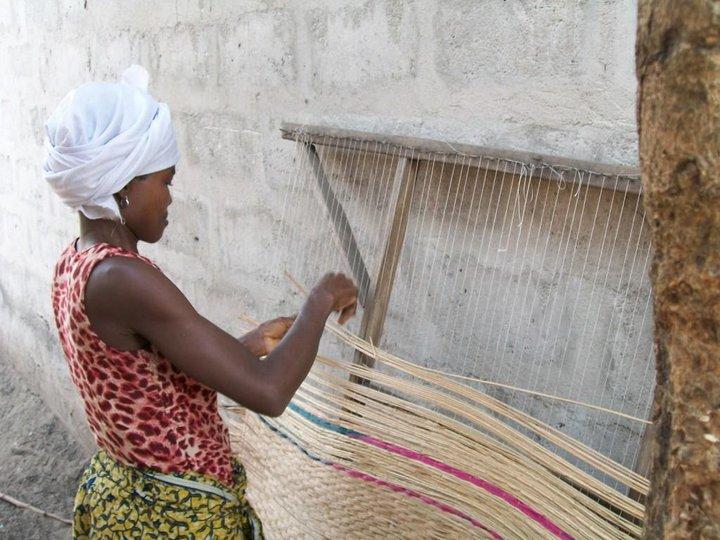 Femme tissant une natte de jonc, sous l'objectif de Joannès Mawuna